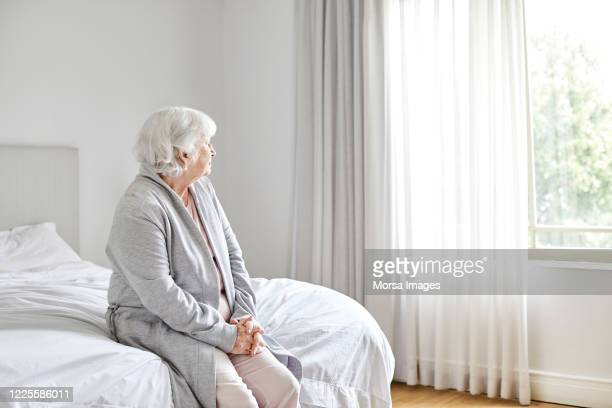 thoughtful elderly female at home during corona - avoidance stock pictures, royalty-free photos & images
