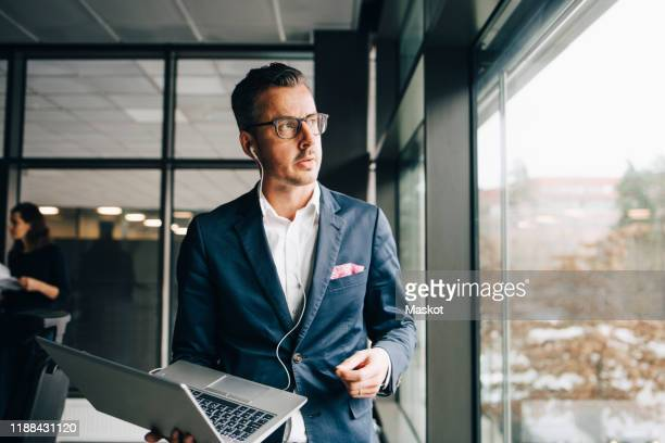 thoughtful entrepreneur holding laptop while looking through window in office - incidental people stock pictures, royalty-free photos & images