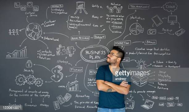 thoughtful entrepreneur looking at the business plan behind him - business plan stock pictures, royalty-free photos & images