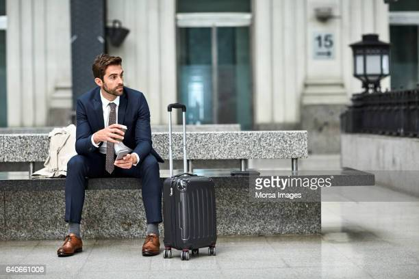 Thoughtful executive holding coffee cup and phone