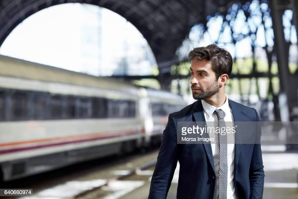 Thoughtful executive standing at railroad station