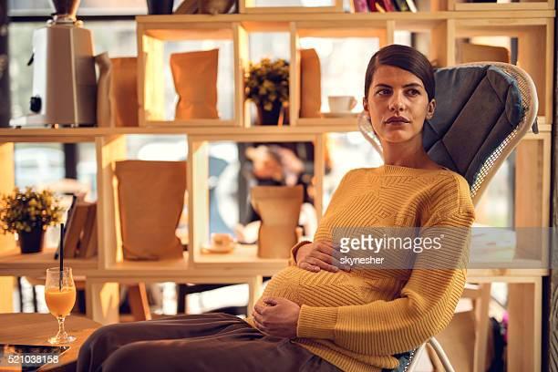 Durchdachte werdende Mutter in einem Café Hände halten am Bauch.