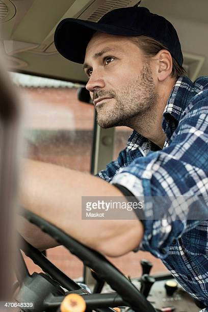 Thoughtful farmer driving tractor