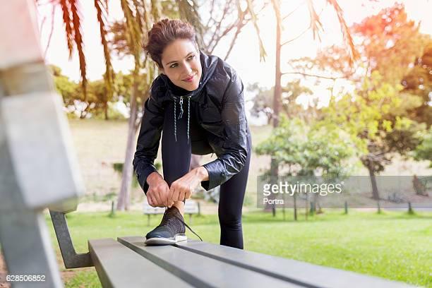 thoughtful female athlete tying shoelace on bench - frau gefesselt stock-fotos und bilder