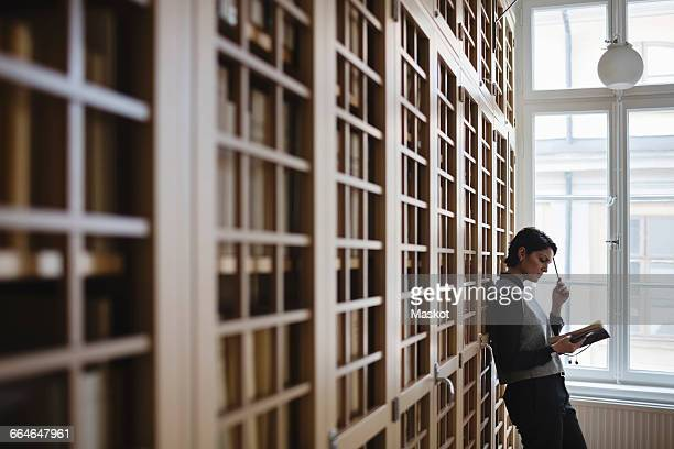 Thoughtful female lawyer researching while leaning on shelf in library