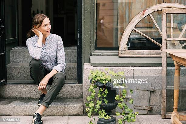Thoughtful female owner sitting on steps at store