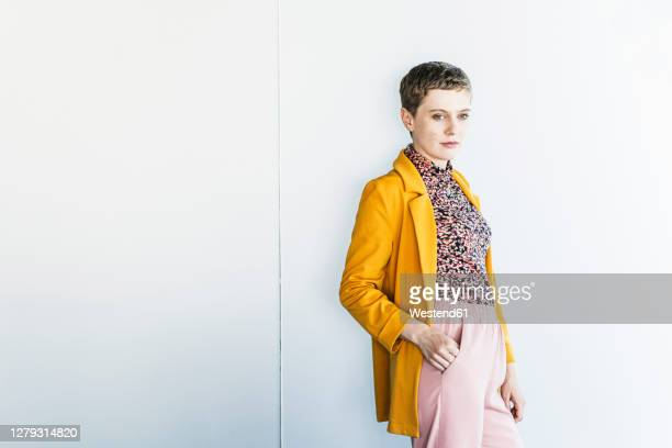 thoughtful female professional standing against white wall in office - hände in den taschen stock-fotos und bilder