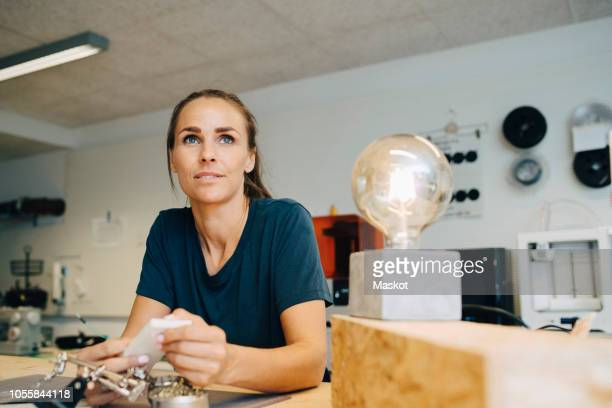 thoughtful female technician looking away while sitting at workbench in creative office - western europe stock pictures, royalty-free photos & images