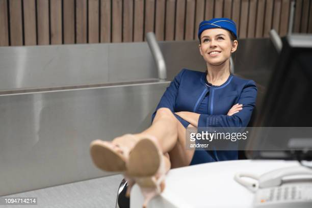 Thoughtful flight attendant relaxing at the counter at the airport