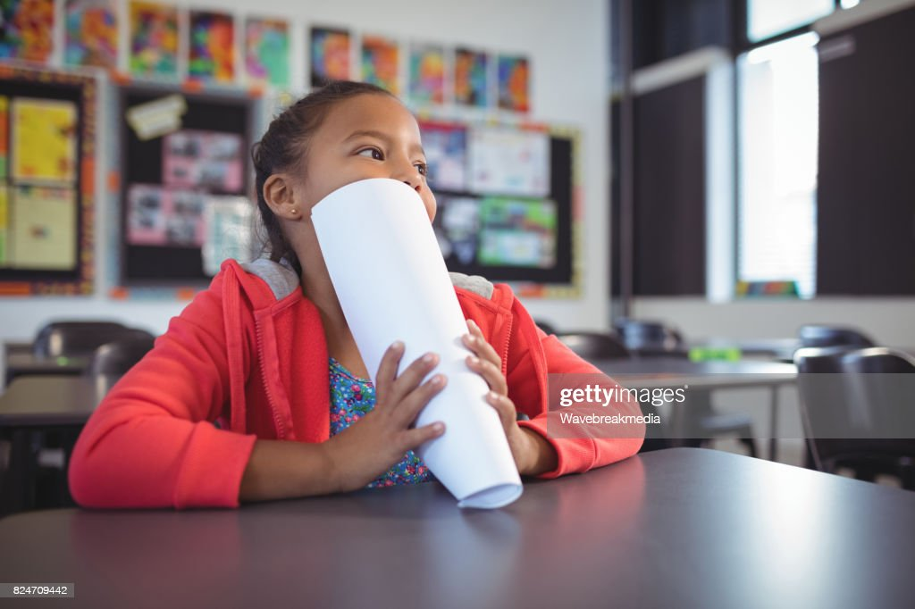 Thoughtful girl covering face with papers while sitting at desk : Stock Photo