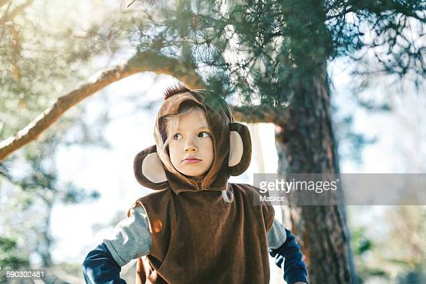 thoughtful girl in monkey suit looking away while standing at yard - animal costume stock pictures, royalty-free photos & images