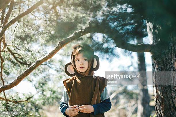 thoughtful girl in monkey suit standing by tree at yard - monkey suit stock pictures, royalty-free photos & images