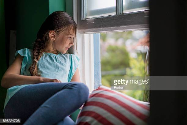 Thoughtful girl looking through window at home