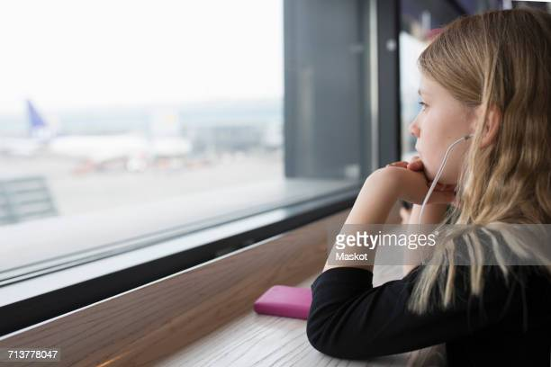 Thoughtful girl looking through window of restaurant