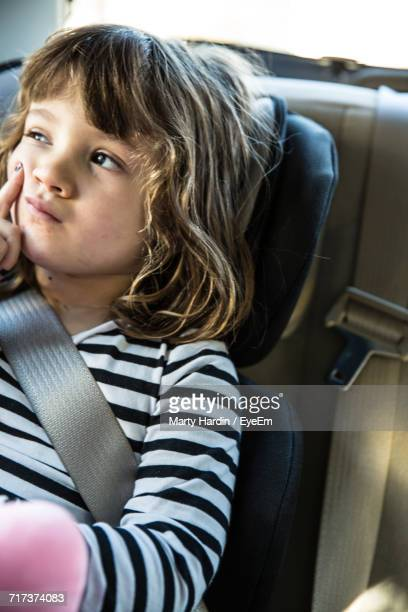 thoughtful girl sitting in car - marty hardin stock photos and pictures