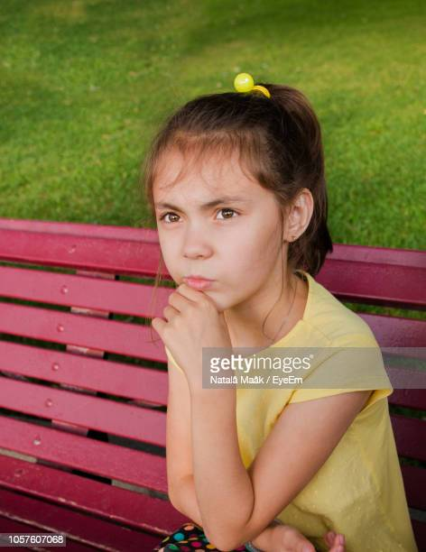 thoughtful girl sitting on bench - hand on chin stock pictures, royalty-free photos & images
