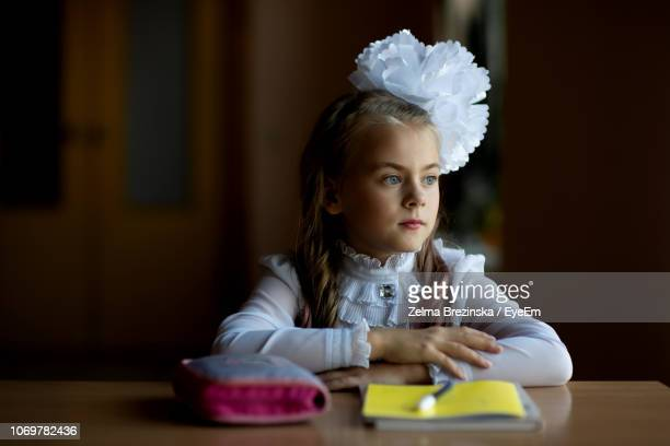 Thoughtful Girl Sitting With Book And Pouch At Desk In School