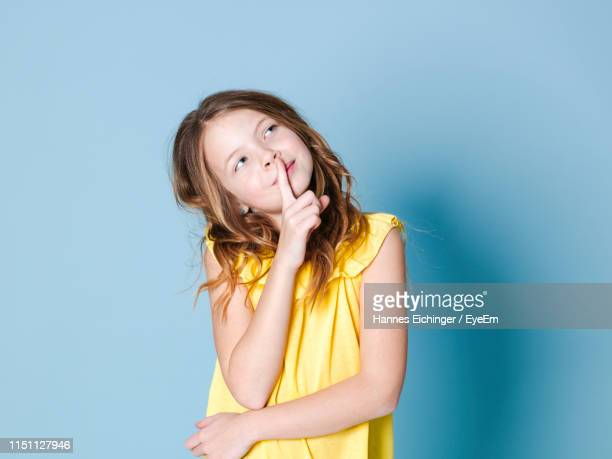thoughtful girl standing against blue background - reflection stock pictures, royalty-free photos & images