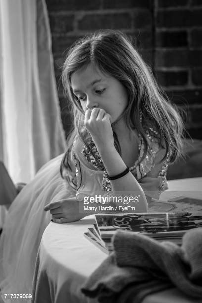 thoughtful girl standing by table at home - marty hardin stock photos and pictures