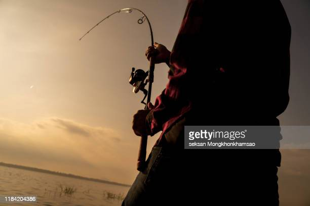 thoughtful guy is sitting at the edge of water and looking to the right. he holds fly rod in hands. it is evening and chilly outside. - pike fish stock pictures, royalty-free photos & images