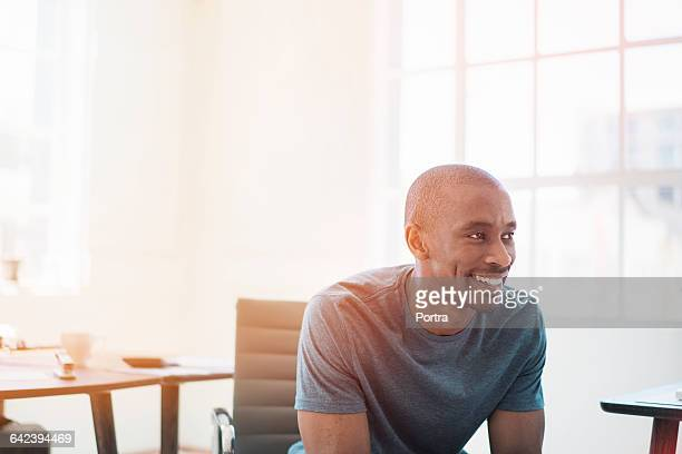 Thoughtful happy businessman in office