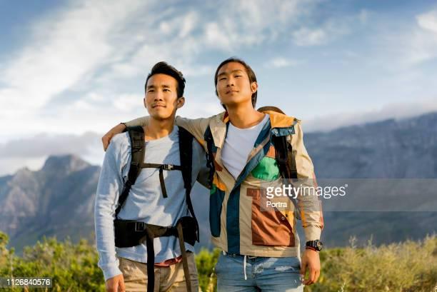 空に対して丘の上に立っている思慮深いハイカー - 若い男性だけ ストックフォトと画像