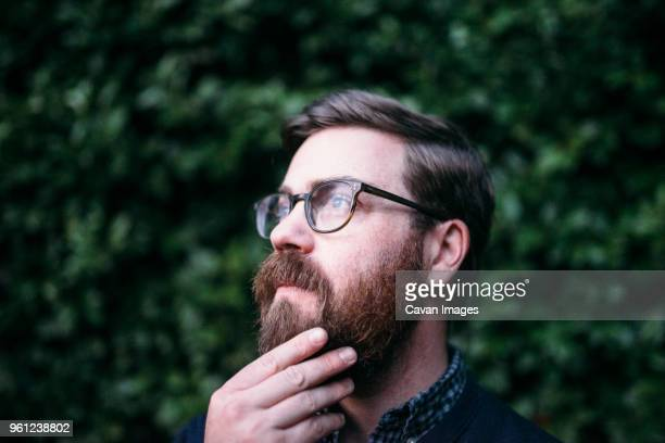thoughtful hipster with hand on chin looking away while wearing eyeglasses against hedge - tête composition photos et images de collection