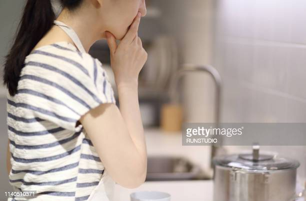 thoughtful housewife with hand on chin - stereotypical homemaker stock pictures, royalty-free photos & images