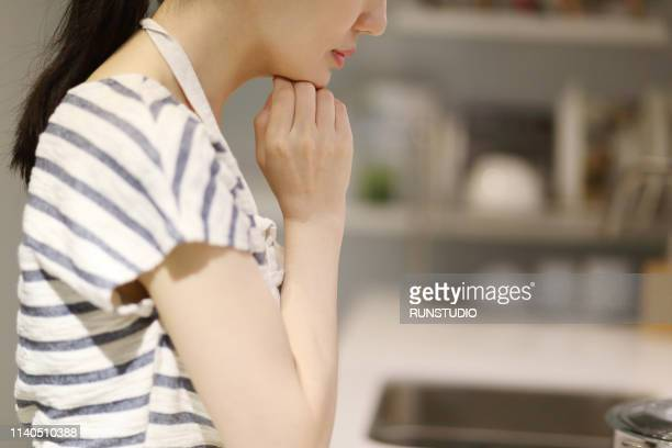 thoughtful housewife with hand on chin - homemaker stock pictures, royalty-free photos & images