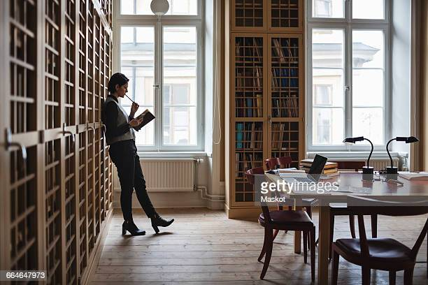 thoughtful lawyer holding book while leaning on shelf in library - law office - fotografias e filmes do acervo