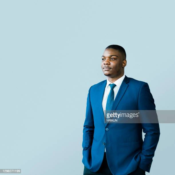 thoughtful male ceo standing with hands in pockets - blue suit stock pictures, royalty-free photos & images