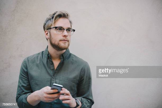 thoughtful male computer programmer holding smart phone against beige wall in office - looking away stock pictures, royalty-free photos & images
