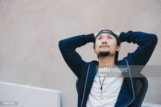 Thoughtful male computer programmer sitting with hands behind head against beige wall in office