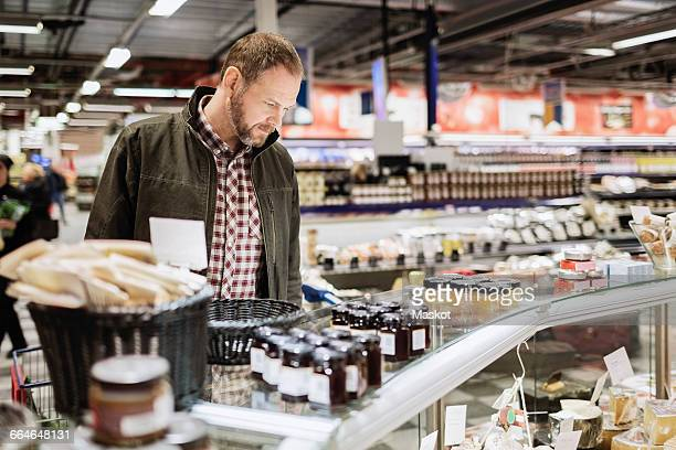 Thoughtful male customer shopping at supermarket
