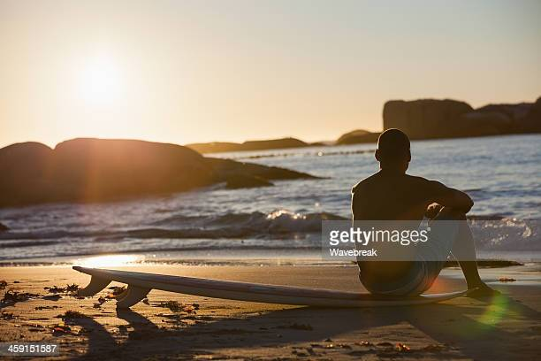 Thoughtful man admiring sunset sitting on his surfboard