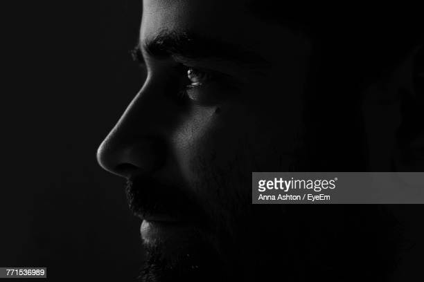 thoughtful man against black background - black and white ストックフォトと画像