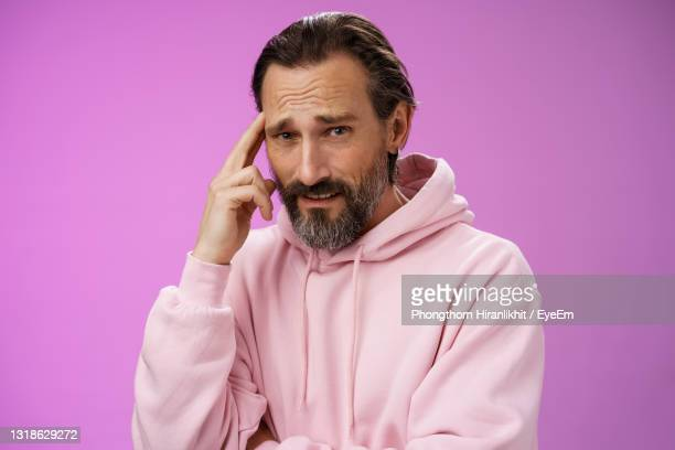 thoughtful man against purple background - 45 49 years stock pictures, royalty-free photos & images