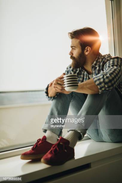 Thoughtful man drinking coffee by the window.