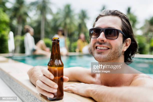Thoughtful man holding beer bottle in swimming pool