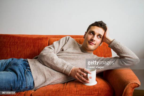 thoughtful man holding coffee cup while lying on sofa at home - nur erwachsene stock-fotos und bilder