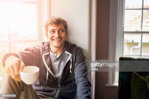 Thoughtful man holding cup while looking away