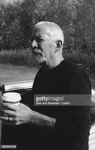 Thoughtful Man Holding Disposable Coffee Cup Standing Near Car