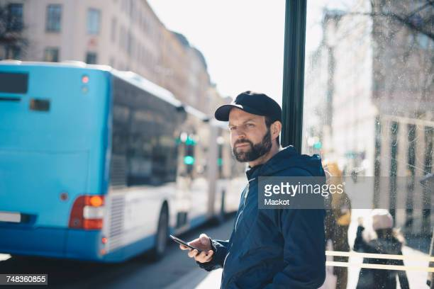 Thoughtful man holding mobile phone while leaning on pole against bus in city