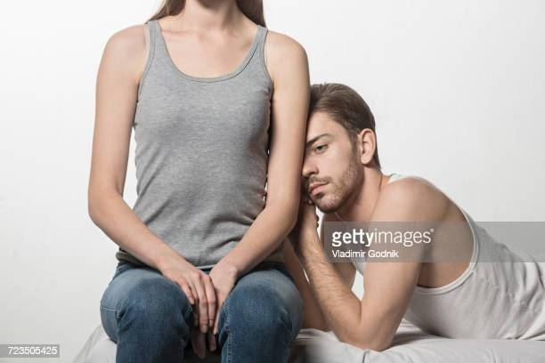 Thoughtful man leaning on girlfriend sitting at bed against white background
