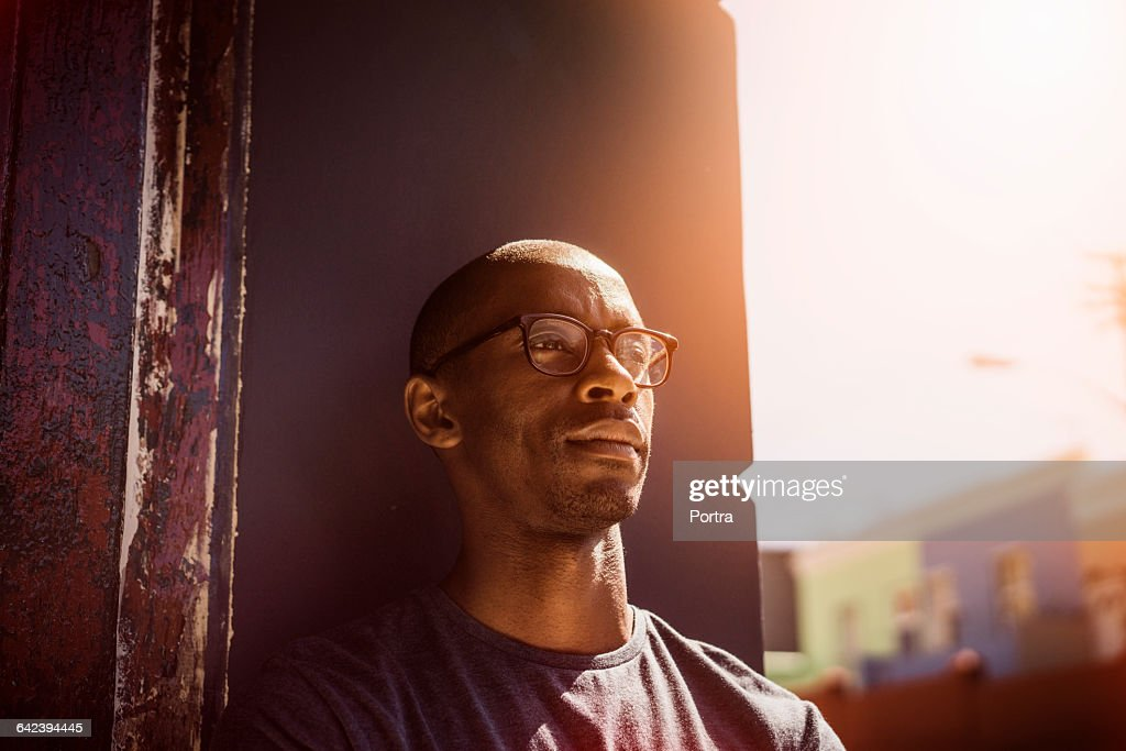 Thoughtful man leaning on wall in city : Stock Photo
