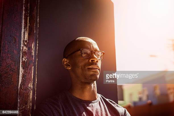 Thoughtful man leaning on wall in city