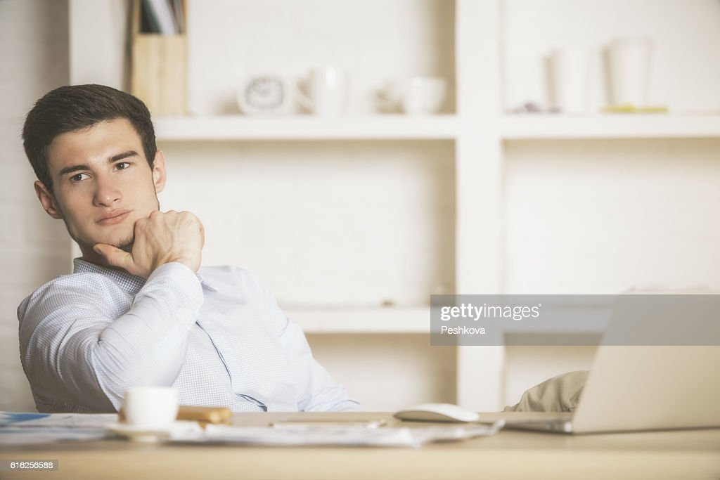 Homem pensativo relaxante no escritório : Foto de stock