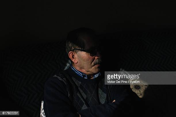 Thoughtful Man Sitting In Darkroom