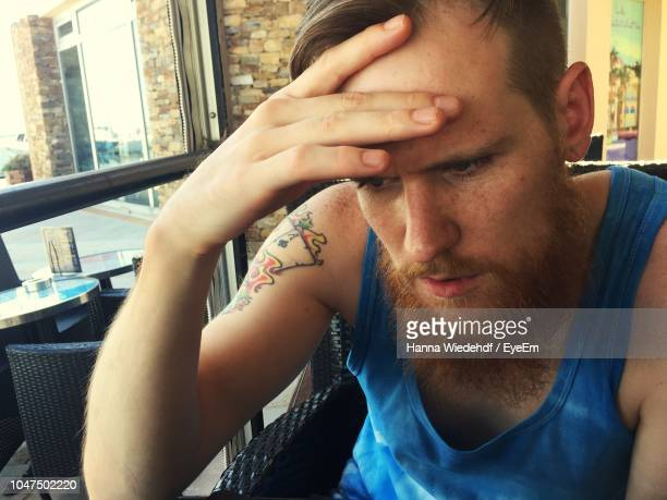 thoughtful man sitting in restaurant - mid adult men foto e immagini stock