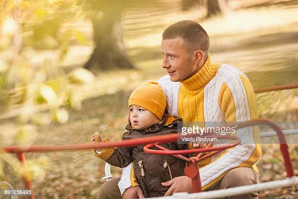 Thoughtful man sitting with baby boy on carousel at park during autumn